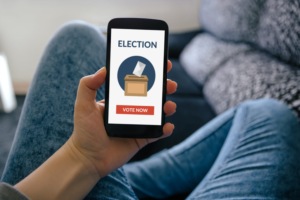 Man holding smartphone and voting online, paperless voting to stop election hacking