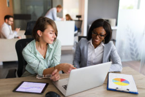 Two businesswomen looking at graphs and data, raise capital concept