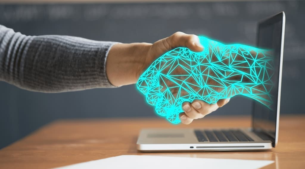 Handshake with one hand coming out of computer screen