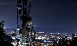 a satellite tower in front of a city landscape at night