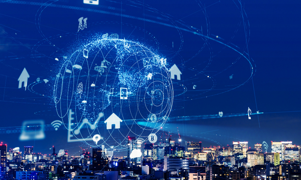 City in the night with a digital model of a blue earth above, with data points scattered across the sky, signifying IoT trends.