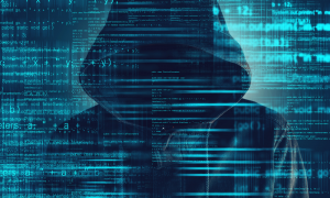 computer hacker with hoodie and obscured face posing cybersecurity risk with computer code overlay.