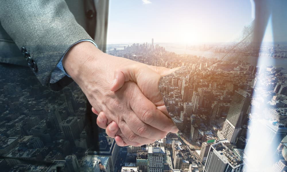 a business handshake in front of a futuristic business skyline